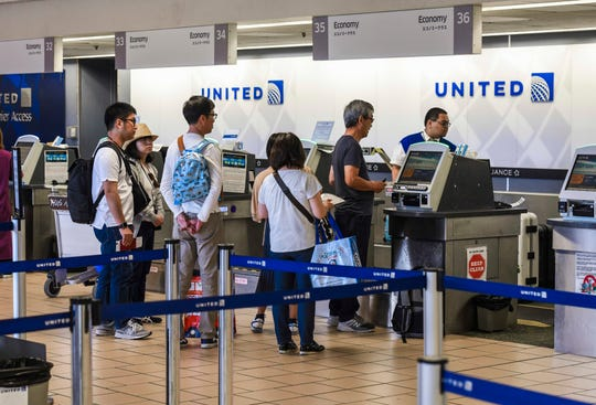 Passengers are assisted by an airline employee while using the self-service kiosk at the United check-in counter at the A.B. Won Pat International Airport in Tamuning Saturday. United has suspended flights from Los Angeles and Houston to Tokyo. There have been no announced changes to Guam-Japan flights.