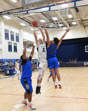 In this file photo from last week, Harvest Christian Academy Eagles player Joe Henderson (33) goes up strong against the Saint Paul Warriors in IIAAG Boys Basketball Feb. 28 at the Family Life Center in Barrigada.