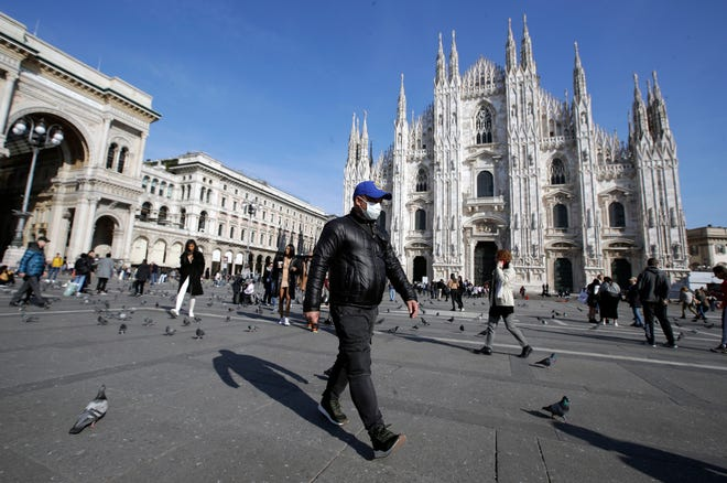 In this Feb. 24, 2020, file photo, a man wearing a sanitary mask walks past the Duomo gothic cathedral in Milan, Italy. Now Italy's streets are almost completely empty as the country tries to fight off COVID-19.