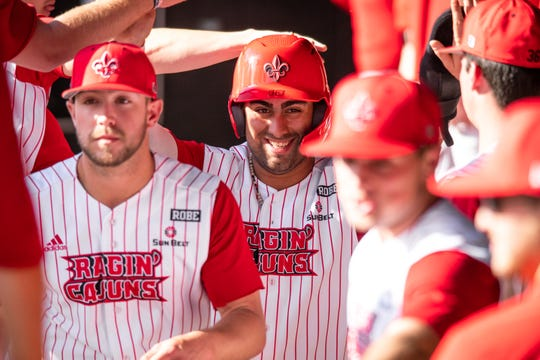 Ragin' Cajuns catcher Sebastian Toro (center) is welcomed back to the dugout after scoring UL's lone run in a 1-0 win over Sam Houston State last Saturday.