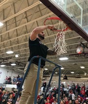 Shelby's first-year coach Nathon Loney snips the last strand of net from the basket after his Whippets win a sectional title by beating Clear Fork 87-67