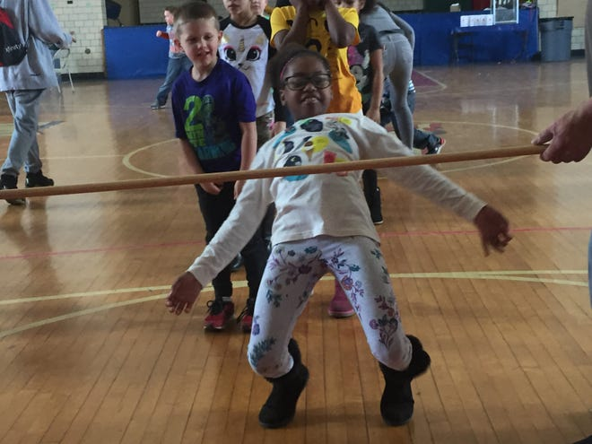Trinitee Taylor does the limbo at Saturday's leap day celebration at the Ocie Hill Neighborhood Center.