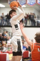 Izard County's Justus Cooper shoots a jumper on Friday night against Viola.