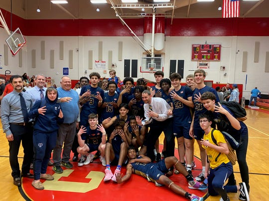The Naples boys basketball team celebrates its 84-78 win over Clearwater in the Class 5A-Region 3 final Friday. The Golden Eagles earned their first regional crown since 1991.