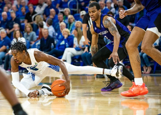 FGCU point guard Jalen Warren (5) loses his footing against North Alabama's Christian Agnew. The Eagles blew a five-point lead with 35.7 seconds left in regulation, then lost in overtime, 78-73, at Alico Arena on Saturday.