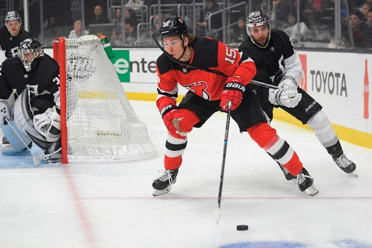 New Jersey Devils center John Hayden, center, moves the puck as Los Angeles Kings center Michael Amadio, right, reaches in while goaltender Jonathan Quick watches during the first period of an NHL hockey game Saturday, Feb. 29, 2020, in Los Angeles.