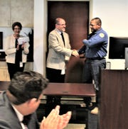Errol Lockett is congratulated by Deputy Director Wastewater, John Mrozek, at the Las Cruces Utilities board meeting on Feb. 13, 2020.