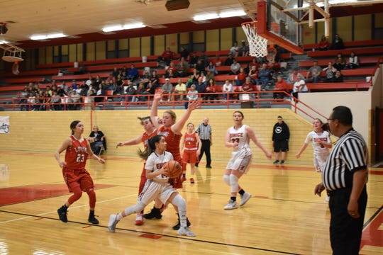 Eunice guard kendra Caballero tries to go around Loving center Mattie Cooksey in the second quarter Friday night in Eunice. The Lady Cardinals defeated the Lady Falcons 48-40 in overtime.