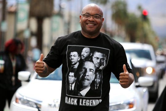 Black History Parade Grand Marshall Waymond Fermon gestures to the crowd as he walks along Palm Canyon Drive in Palm Springs, Calif., on Saturday, February 29, 2020.
