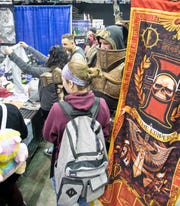 Patrick Olson - Inquisitor from Warhammer 40k - and his wife Chey Olson, of Valdez, Alaska, check out merchandise during PensaCon at the Pensacola Bay Center on Friday, Feb.28, 2020.
