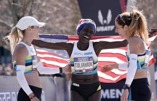 Aliphine Tuliamuk of Flagstaff won the U.S. Olympic Marathon Trials women's title Saturday. She celebrates with her Northern Arizona Elite teammates Kellyy Taylor, left, and Stephanie Bruce, who also were in the top 10.