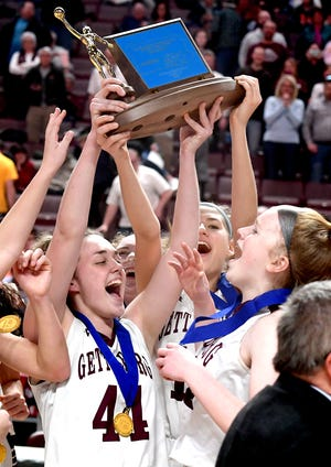 Gettysburg's players, from left, Taylor Richardson, Lily Natter and Autumn Oaster hoist the trophy after beating Twin Valley in the District 3 Class 5-A girls' basketball title game at the Giant Center Friday, Feb. 28, 2020. Gettysburg won 46-40. Bill Kalina photo,