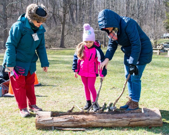 From left, volunteer Rita Buschman, Leah Riddle, 5, and Suzy Riddle learn to make syrup the old fashioned way during the York County Department of Parks and Recreation's Maple Sugar Festival Days.