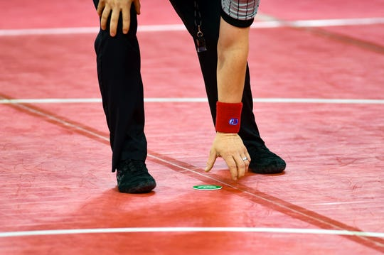 An official flips a coin to see who starts in which position during a match at the state wrestling semifinals on Friday, Feb. 28, at the Denny Sanford Premier Center in Sioux Falls.