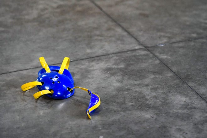 A wrestler's headgear lies on the concrete floor during the high school state semifinals on Friday, Feb. 28, at the Denny Sanford Premier Center in Sioux Falls.