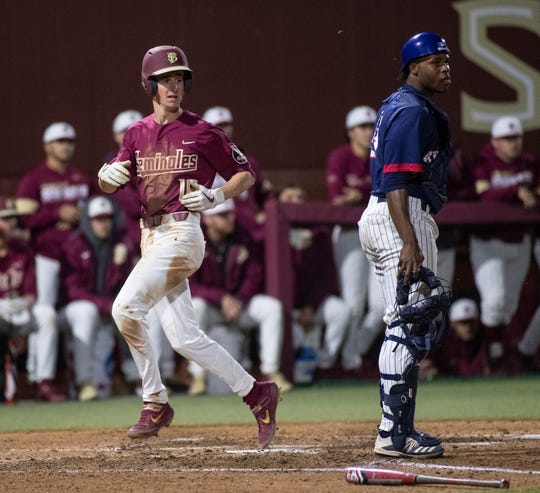 Florida State Seminoles infielder Tyler Martin looks back at his teammates rounding the bases as he tags home plate. The Florida State Seminoles beat the Florida Atlantic Owls 5-1, Friday, Feb. 28, 2020.