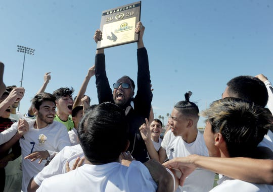 Head coach Adrian Garcia holds up the championship plaque while being surrounded by his players after Channel Islands defeated St. John Bosco 2-1 in overtime in the CIF-Southern Section Division 2 championship game Saturday at Warren High in Downey.
