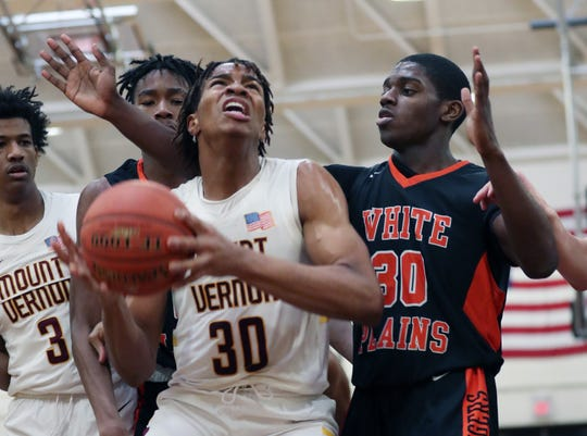 Mt. Vernon's Troy Hupstead (30) goes up for a shot in front of White Plains' Quion Burns (0) and Elijah Pierre (30) during boys basketball playoff action at Mt. Vernon High School  Feb. 28, 2020. Mt. Vernon won the game 66-56.