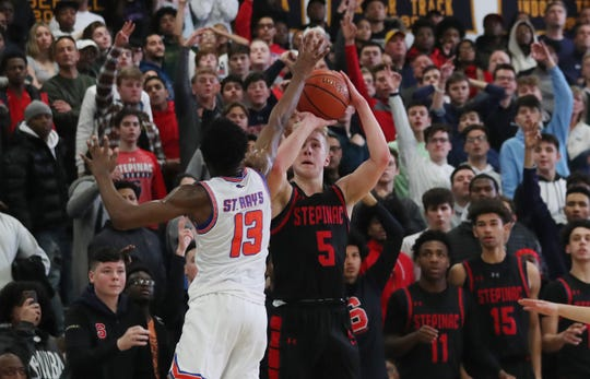 Stepinac's Luke Fizulich (5) hits a 3-point shot in front of St. Ray's Gary Grant (13)  during second half action in the CHSAA_NYC title at Mount Saint Michael Academy Feb. 29, 2020. Stepinac won the game 73-68.