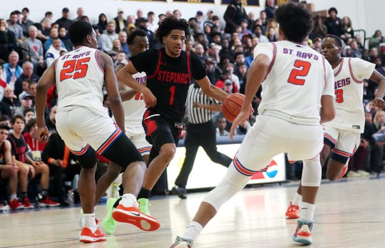 Stepinac's R.J. Davis is surrounded by St. Ray's defenders  during action in the CHSAA_NYC title at Mount Saint Michael Academy Feb. 29, 2020. Stepinac won the game 73-68.