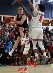 Stepinac's Luke Fizulich (5) drives to the basket in front of St. Ray's Luis Kortright (2) during second half action in the CHSAA_NYC title at Mount Saint Michael Academy Feb. 29, 2020. Stepinac won the game 73-68.