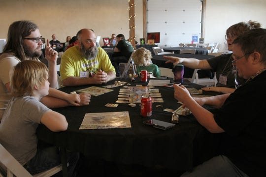 A family, consisting of Ronan, left, Josh Thomas, Matt Bakerm Briar, Toni Thomas and Mimi Baker play Dice Forge Saturday, Feb. 29, 2020, at Fallscon held at the French Country Meadow in Wichita Falls.