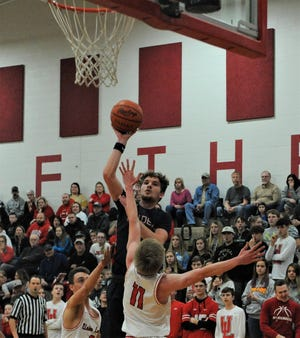 Morgan's Carver Myers puts a shot over Belmont Union Local's Nathan Meyer in Friday's Division III sectional final. The Raiders won 49-46 in triple overtime.