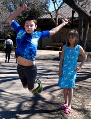 Colton Mullins, 10, tries his best to match the 14-foot distance while his sister Annabella, 9, waits her turn Saturday.