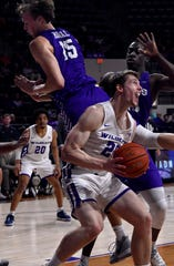 Hayden Howell feints as Central Arkansas defenders fly past him, then jumps for the basket during ACU's game at home in Moody Coliseum Saturday.
