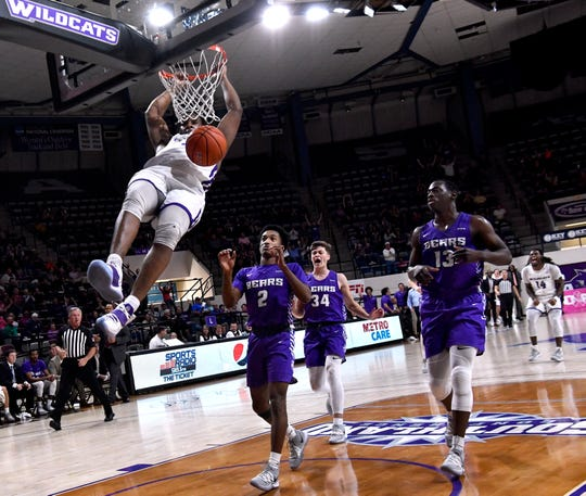 ACU forward Airion Simmons hangs from the rim after dunking the ball against Central Arkansas Saturday in Moody Coliseum. Final score was 75-70, ACU.