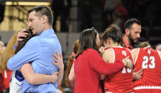 Veribest coach Chris Schlicke, near left, hugs Madison Dunn while Hermleigh players are being consoled in the background after the Lady Falcons knocked off the two-time defending region champs 27-25 in the Region II-1A championship game Saturday, Feb. 29, 2020, at ACU's Moody Coliseum.