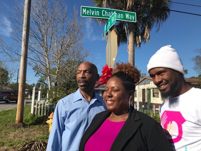 The son, Michael Chatman, daughter, Kim Chatman and grandson, Anthony Chatman, of Pastor Melvin Chatman stand in front of new roadsign.