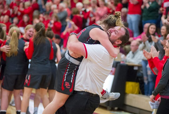 Taylor Ratliff gives coach Abram Kaple a hug after beating Seneca East in the D-IV district championship.