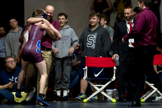 Spaulding's Caleb Hunington, left, leaps into the arms of coach Matt Thurston after winning the 106-pound final of the Vermont high school wrestling championships in Bennington on Saturday, Feb. 29, 2020.