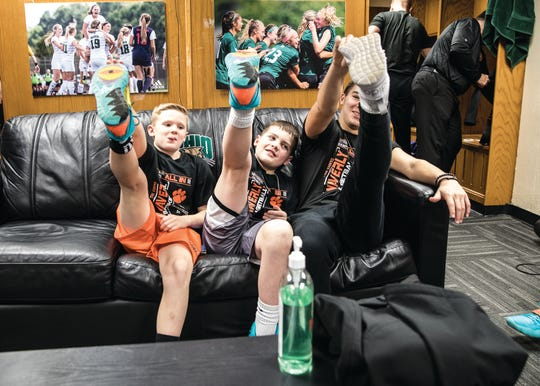 (L-R) Ball boys Kai Keese and Kage Alexander try to mimic Weston Roop and other Waverly Tiger players as they stretch before a Division II districts semifinals games against Warren High School on Feb. 29, 2020, in Athens, Ohio.