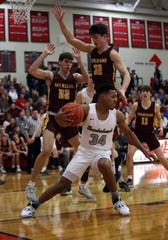 Lakota East guard Nate Johnson looks to pass as Turpin's Josh Bell [32] and Owen Spencer provide defense Feb. 29 in the Division I district semifinal game.