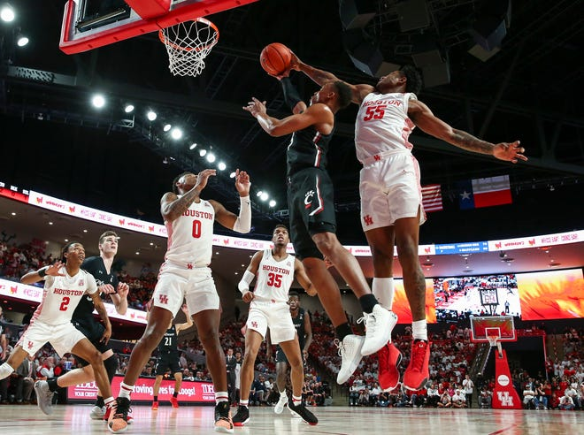 Mar 1, 2020; Houston, Texas, USA; Cincinnati Bearcats guard Mika Adams-Woods (3) shoots against Houston Cougars center Brison Gresham (55) during the first half at Fertitta Center.