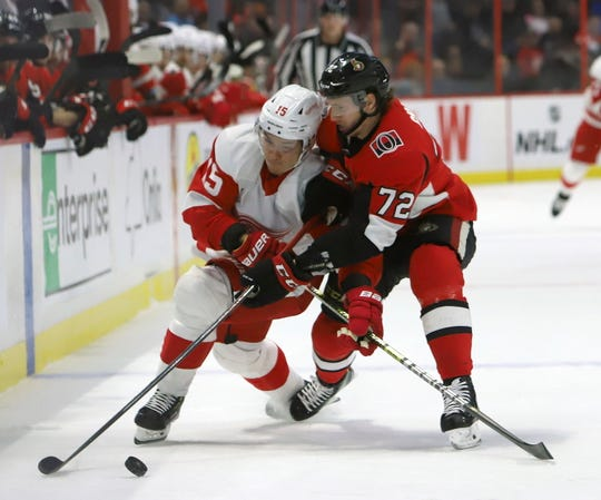 Detroit Red Wings left wing Dmytro Timashov battles for control of the puck with Ottawa Senators defenseman Thomas Chabot during first period in Ottawa, Saturday, Feb. 29, 2020.
