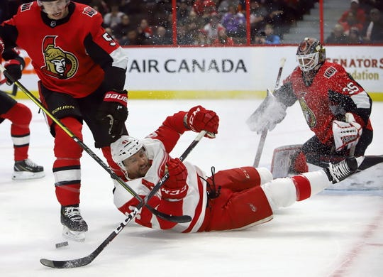 Detroit Red Wings' Luke Glendening is knocked down by Ottawa Senators' Mike Reilly as goaltender Marcus Hogberg looks on during the first period in Ottawa, Saturday, Feb. 29, 2020.