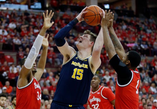 Michigan center Jon Teske goes up for a shot between Ohio State forward Kaleb Wesson, left, and guard Luther Muhammad during the first half in Columbus, Ohio, Sunday, March 1, 2020.