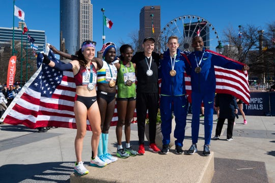 U.S. Olympic marathon qualifiers, from left, Molly Seidel, Aliphine Tuliamuk and Sally Kipyego, and Jacob Riley, Galen Rupp and Abdi Abdirahman, pose for photos after Saturday's trials.