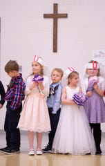 """Kindergartners wait for their wedding pictures to be made by their parents after the marital union of the letters """"Q"""" and """"U"""" at Good Shepherd Catholic School Friday afternoon."""