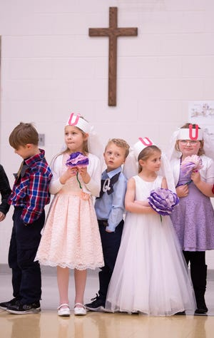 "Kindergartners wait for their wedding pictures to be made by their parents after the marital union of the letters ""Q"" and ""U"" at Good Shepherd Catholic School Friday afternoon."