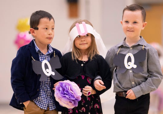 """William """"Q"""" Gonzales, left, Lea """"U"""" Hobbs and Evan """"Q"""" Rhymer walk down the aisle at the Q and U wedding at Good Shepherd Catholic School Friday afternoon. Since the boys outnumbered the girls, some of the girls wound up with two boys."""