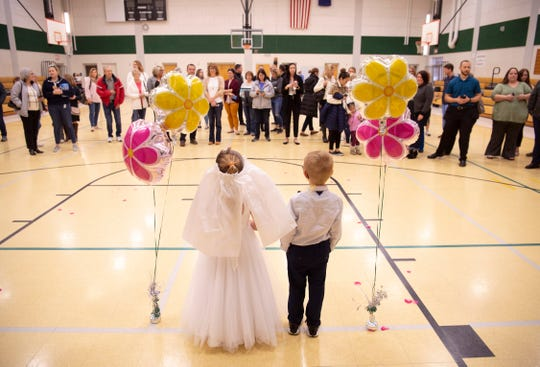 """Kindergartners Kinley """"U"""" Hasenour and Daniel """"Q"""" Frounfelterat pose for marriage portraits after the union of letters Q and U at Good Shepherd Catholic School Friday afternoon."""