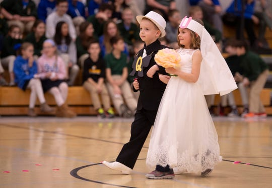 """Riley """"Q"""" Lincoln and Lucy """"U"""" Lovell walk down the aisle for the Q and U wedding at Good Shepherd Catholic School Friday afternoon."""
