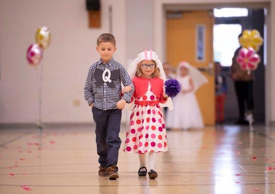 "Holden ""Q"" VanWynsberghe and Emma ""U"" Fehrenbacher walk down the aisle during the Q and U wedding at Good Shepherd Catholic School Friday afternoon."