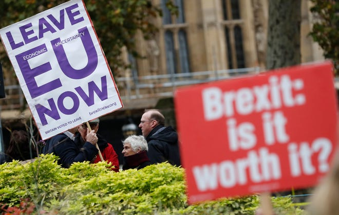 Pro and anti-Brexit protesters hold placards as they vie for media attention near Parliament in London.
