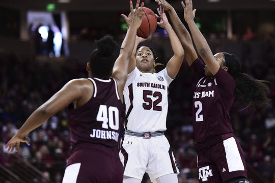 South Carolina guard Tyasha Harris (52) attempts a shot against Texas A&M guard Aaliyah Wilson (2) and Ciera Johnson (40) during the first half of an NCAA college basketball game Sunday, March 1, 2020, in Columbia, S.C. (AP Photo/Sean Rayford)