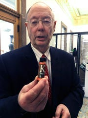 "In this Thursday, Feb. 27, 2020 photo, Glenn Lautzenhiser holds a bottle of a drink containing a drug called kratom at the Mississippi Capitol in Jackson, Miss. Lautzenhiser, who has volunteered in prison ministry, wants Mississippi to outlaw kratom, saying: ""This stuff destroys lives and destroys families."" He is a resident of Columbus, Miss."